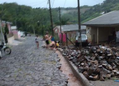 Moradores de Herval arrancam parte do calçamento da rua para impedir que a água da chuva invadisse novamente suas casas